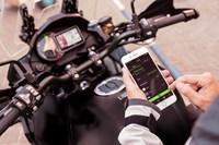 Piloto que usa RIDEOLOGY THE APP en el teléfono de su motocicleta Kawasaki